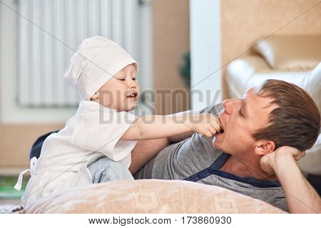 Young boy in doctor uniform playing with father and examining his throat