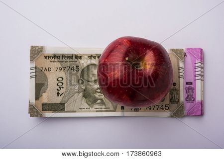 indian new currency notes of 500 and 200 rupees with fresh red apple and stethoscope - India and healthcare concept