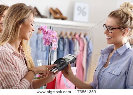 Women buying clothes in clothes store