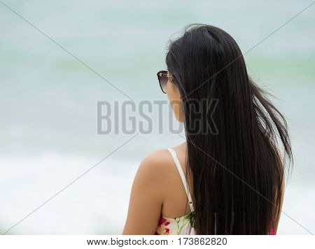 Young beautiful woman standing back to camera and looking at the sea waves. Freedom loneliness summer time or vacations concept