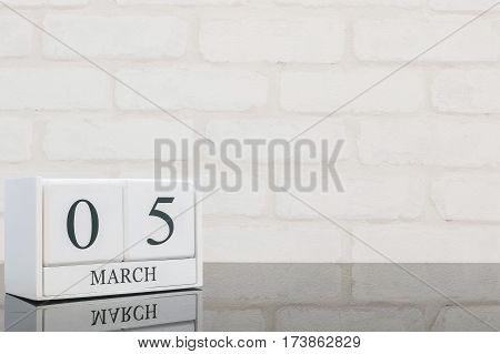 Closeup white wooden calendar with black 5 march word on black glass table and white brick wall textured background with copy space selective focus at the calendar