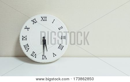 Closeup white clock for decorate show half past five p.m. or 5:30 p.m. on white wood desk and cream wallpaper textured background with copy space