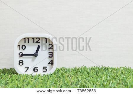 Closeup white clock for decorate show a quarter to one o'clock or 12:45 a.m. on green artificial grass floor and cream wallpaper textured background with copy space