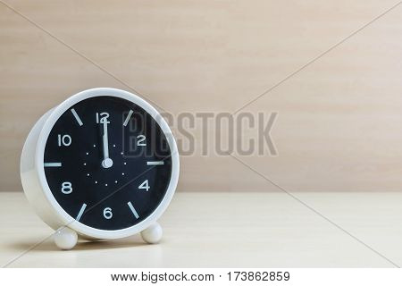 Closeup alarm clock for decorate in 12 o'clock on brown wood desk and wall textured background with copy space