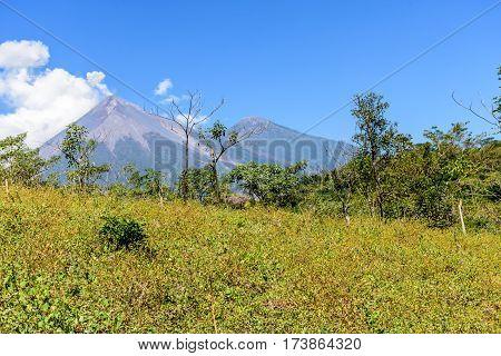 Active Fuego volcano puffs smoke with Acatenango volcano behind in Escuintla, Guatemala, Central America