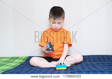 child playing car gameboy playing with toys sitting on bed indoorkid holding two toy cars at home alone