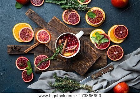 Mulled wine with slice of red orange, fresh rosemary and spices. A cup with hot drink, top view