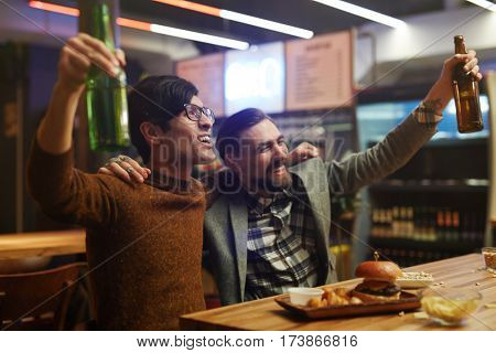 Ecstatic men with beer celebrating victory of football team