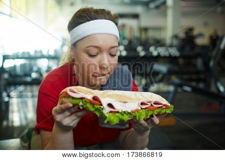 Portrait of cute overweight woman licking her lips wanting to eat huge fattening sandwich while working out in gym, struggling to stay in shape