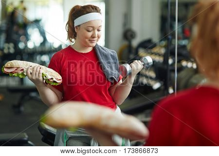 Portrait of cute overweight woman doing weight exercises with huge fat sandwich in one hand and dumbbell in other while working out in gym , difficult decision in dieting