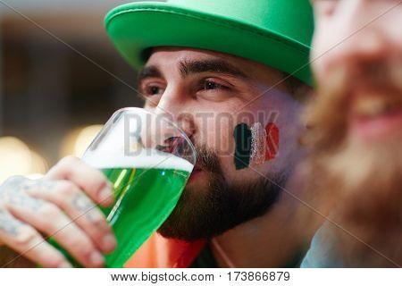 Guy in green hat drinking beer