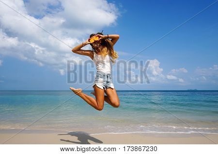 Pefect Vacation Concept. Summer travel. Young beautiful funny model holding orange in front eyes with smile jumping on the beach in sunny day