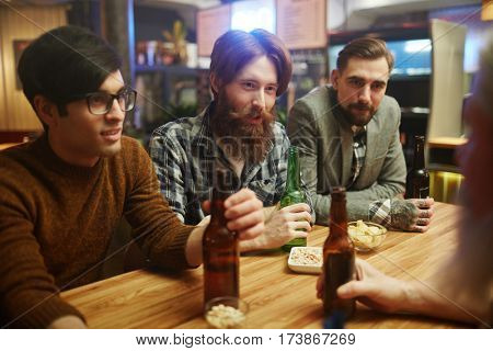 Male buddies with bottles of beer having rest in pub