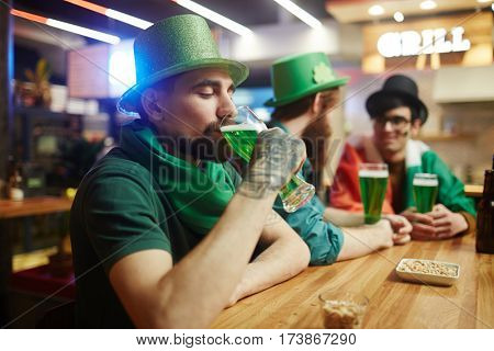Young man enjoying beer on background of his buddies talking