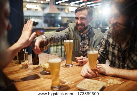 Cheerful buddies having beer on St Patrick day
