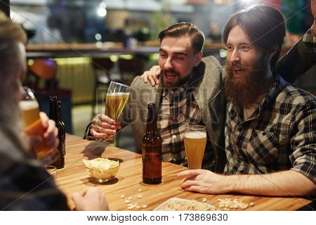 Drunk buddies cheering with beer and talking by table in pub