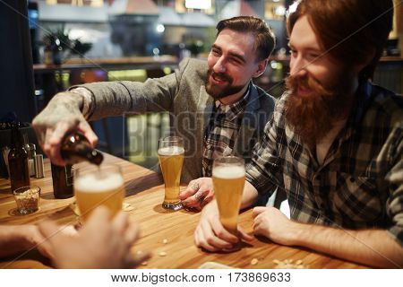Happy man pouring beer in glass for his buddy