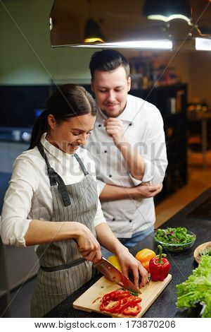 Girl cooking slow food with chef near by