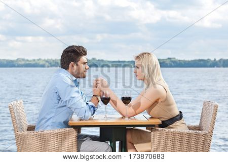 Young couple holding hands while looking at each other at outdoor restaurant by lake