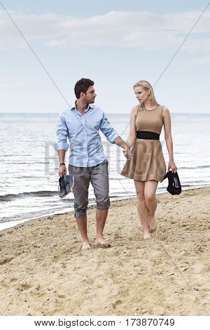 Full length of romantic young couple holding hands and walking on beach