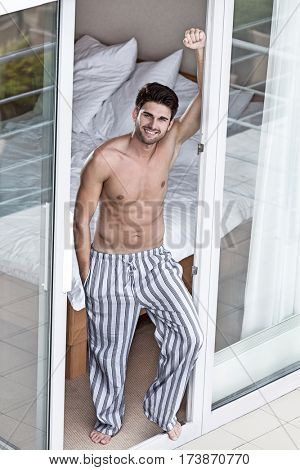Full length portrait of handsome young man standing at balcony doorway