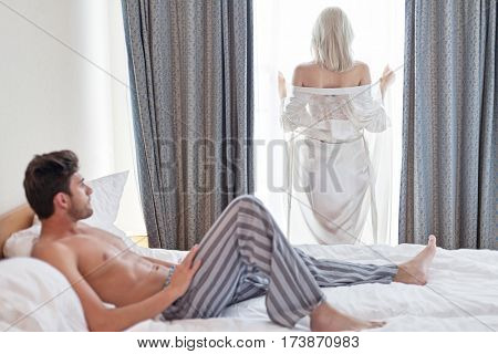 Full length of shirtless young man looking at woman standing by hotel window