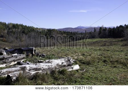 Wide view of Sutton peaks with autumn trees of colorful fall foliage cut logs in front/left of the frame on a beautiful bright sunny day in October near the town of Sutton in the Eastern Townships of Quebec.