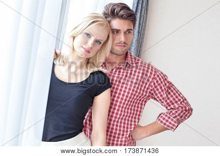 Portrait of beautiful young woman with man at window in hotel room