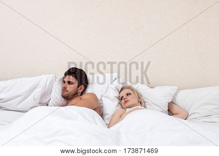 Angry young man ignoring woman in bed