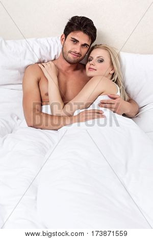 Portrait of happy young couple spending quality time in bed