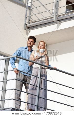 Smiling young man with woman having coffee at hotel balcony