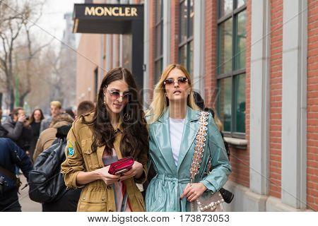 MILAN ITALY - FEBRUARY 23: Fashionable women pose outside Fendi fashion show during Milan Women's Fashion Week on FEBRUARY 23 2017 in Milan.