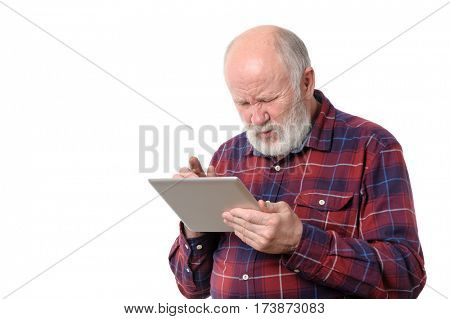Senior bald and bearded white haired man squints and touching something at tablet computer screen, isolated on white background