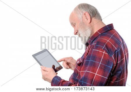Senior bald and bearded white haired man smiling while doingsomething at screen of tablet computer, isolated on white background