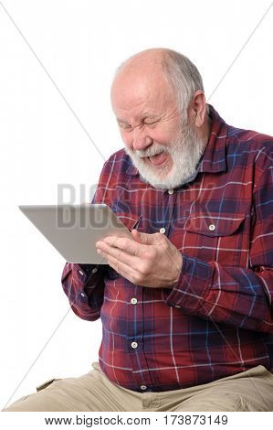 Senior bald and bearded white haired man laughing loud with something at screen of tablet computer, isolated on white background