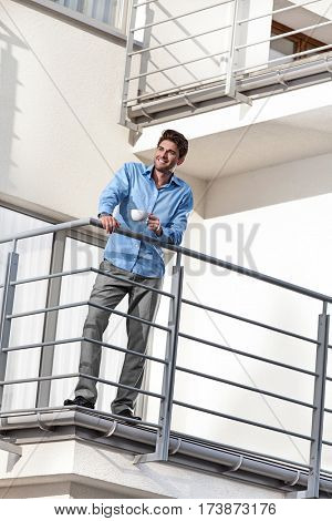 Full length of smiling young businessman having coffee at hotel balcony