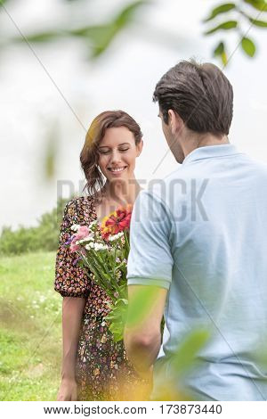 Rear view man giving flowers to woman in park