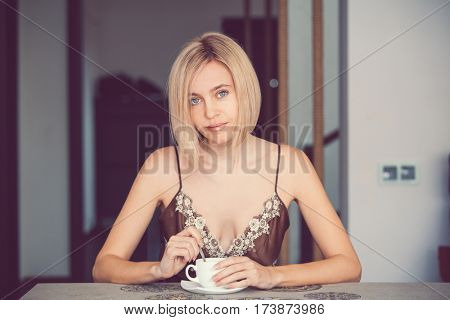 Female in a home clothes drinking coffee. Woman in nightie morning