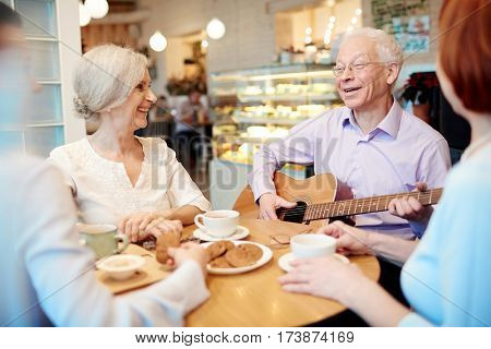 Cheerful senior buddies having merry time in cafe