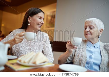 Female buddies with cups drinking tea and talking