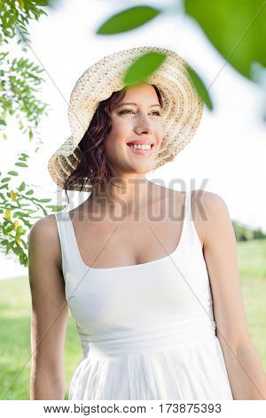 Thoughtful young woman in sundress and hat standing in park