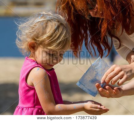 Adult woman pours out from the pack paint Holi to hands of a little girl.