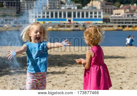 Little blond girls of three years playing with paint Holi hold and throw the powder up play happy and laughing.