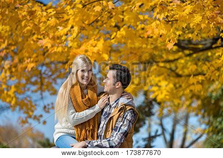 Portrait of happy woman sitting on man's lap in park during autumn