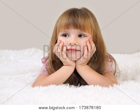 The child was conceived. Portrait of a beautiful little girl. White fluffy blanket. Long blonde hair