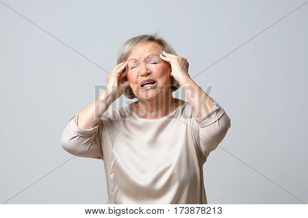 Senior Woman With Her Hands To Her Temples