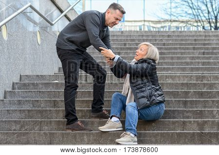 Man Helping Woman To Get Up