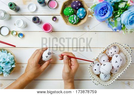 Top view happy Easter festival background.Design handmade father painting cute easter eggs for chil on rustic white wooden and decoration beautiful flower color with copy space.