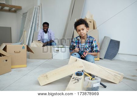 Little boy with power-tool looknig at camera in new house