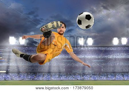 Young soccer player kicking ball in midair inside stadium